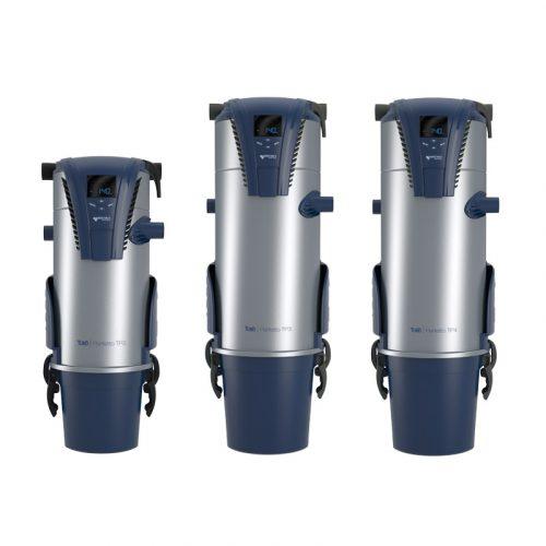Eine Reihe von drei Tubo Zentralsauggeräte. Die Oberfläche ist matte Metallfarbe, die Unter- und Oberteilen sind dunkelblau Kunststoff. Auf dem oberen Teil eine LED-Anzeige.